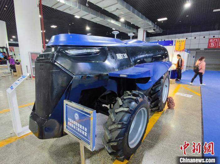 """图为一带一路""""(洛阳)国际农业合作博览会上,展出的多用途智能新能源轮式拖拉机,可进行耕、耙、播、收等作业。"""