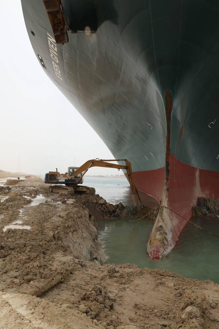 """埃及运河搁浅巨轮旁""""渺小""""挖掘机的工人:面对梗图笑不起来"""